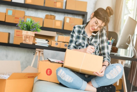 Young ecommerce business woman preparing items for shipping.