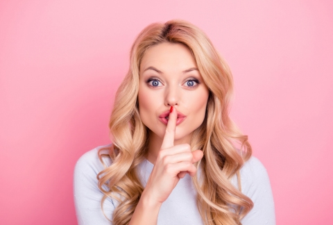 Lady holding her finger to lips to stop you talking.