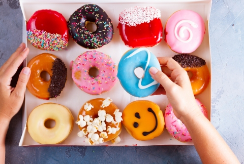 Choosing a doughnut from a colourful box full.