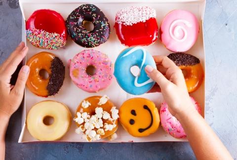 Choosing a doughnut from a colourful box full.