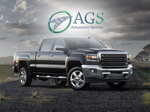 Black truck on gravel road with AGS logo in forefront.