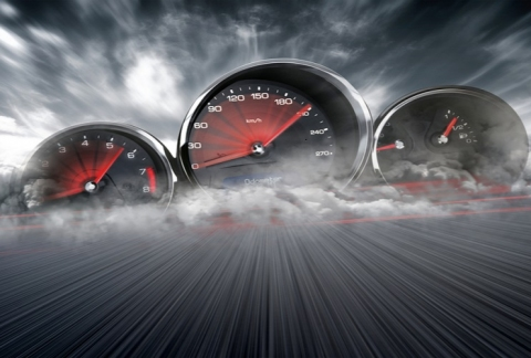 Three speedometers on a dusty race track