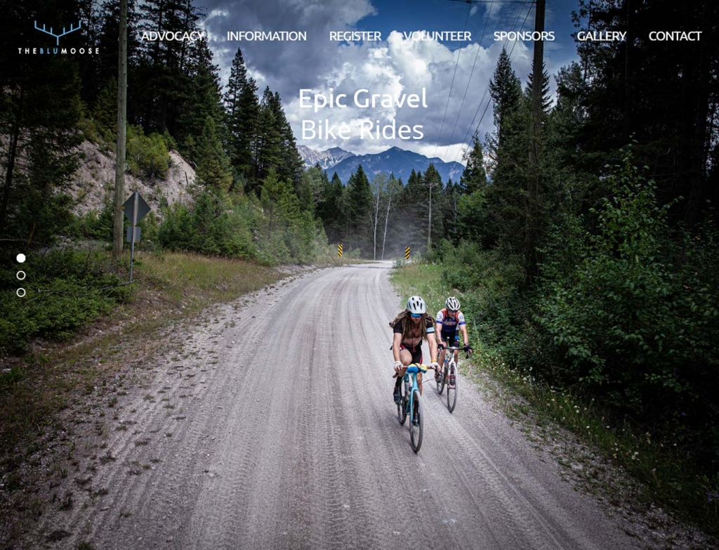 Cyclists on a track road in mountains on website home page