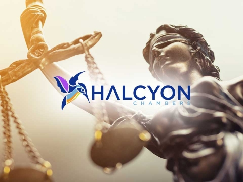 Halcyon logo set against statue holding scales of law.
